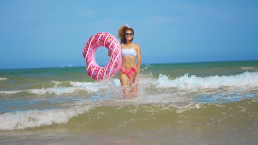 deli : Young woman having fun with toy Inflatable ring donut on the beach.