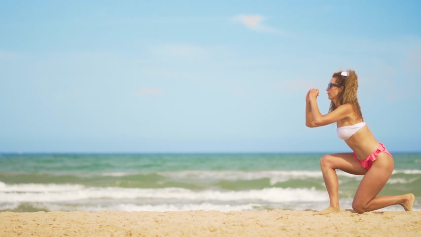executar : A girl in a bathing suit plays sports against the backdrop of the sea. Effective exercises for the buttocks.