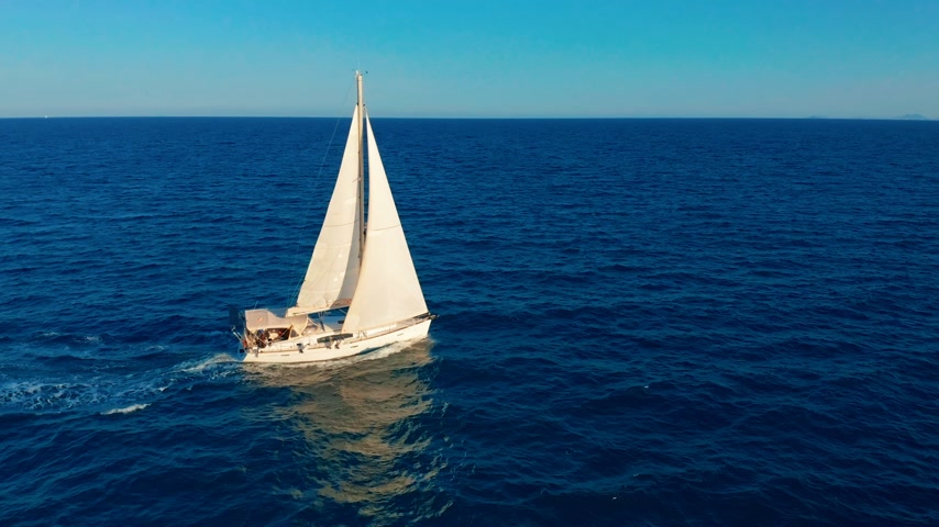 földközi tenger : Sailboat in the ocean. White sailing yacht in the middle of the boundless ocean. Aerial view. Stock mozgókép