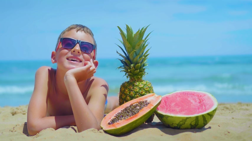 piknik : smiling boy lies on the seashore with a composition of exotic fruits against the sea.