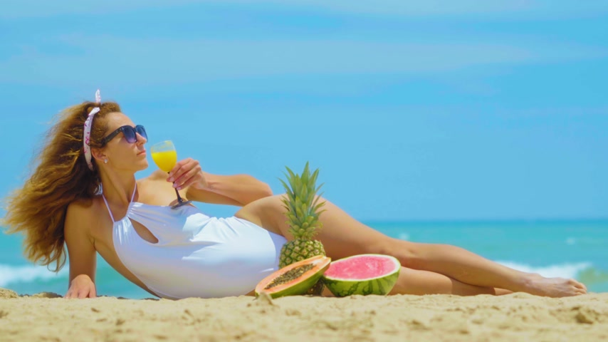 relaks : The woman drinks fresh orange juice background the sea. Young beautiful woman lying by the sea on the sand, drinks orange fresh juice. Concept vacation. Wideo