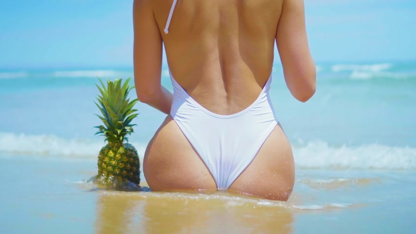 pažba : Closeup beautiful sexy young woman siting on the beach with pineapple. Sexy womans buttocks in white bikini, slim womans figure on the beach with sky and sea background. Woman enjoys summer vacation.