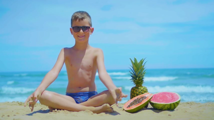 meditál : A boy sits and meditates on the seashore near exotic fruits against the background of the sea.