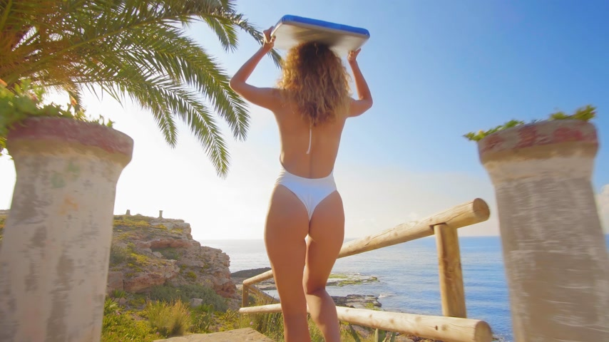 recreatie : Beautiful young woman surfer walking down beach at sunset. Stockvideo