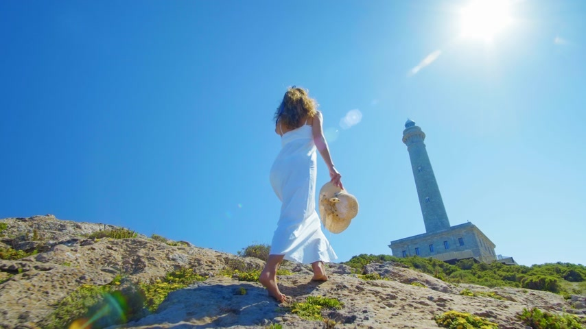 freedom tower : Girl walking to lighthouse then stops and looking at him Stock Footage