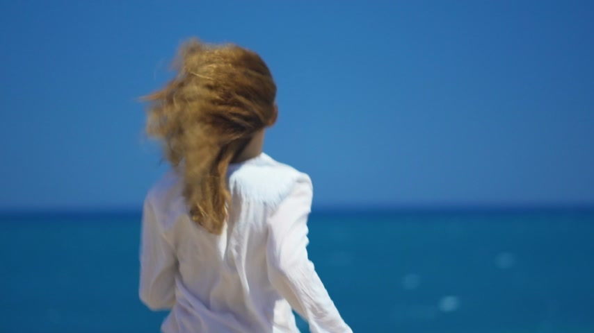 alpes : A young girl runs up to the cliff above the beautiful sea. Beautifully develop hair in the wind. Stock Footage