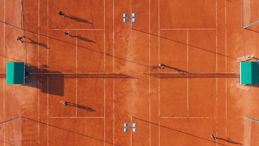 upward : Aerial top view of unrecognizable tennis players playing tennis on the orange court on a sunny summer day. Stock Footage