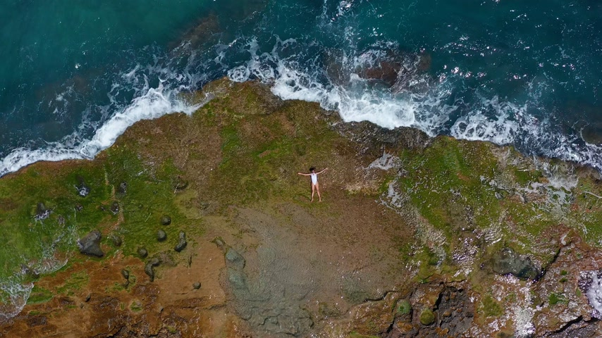 tyrkysový : AERIAL VIEW. Sea waves splashing with foam and spray to stony coast. Beautiful woman lies on rocky beach.