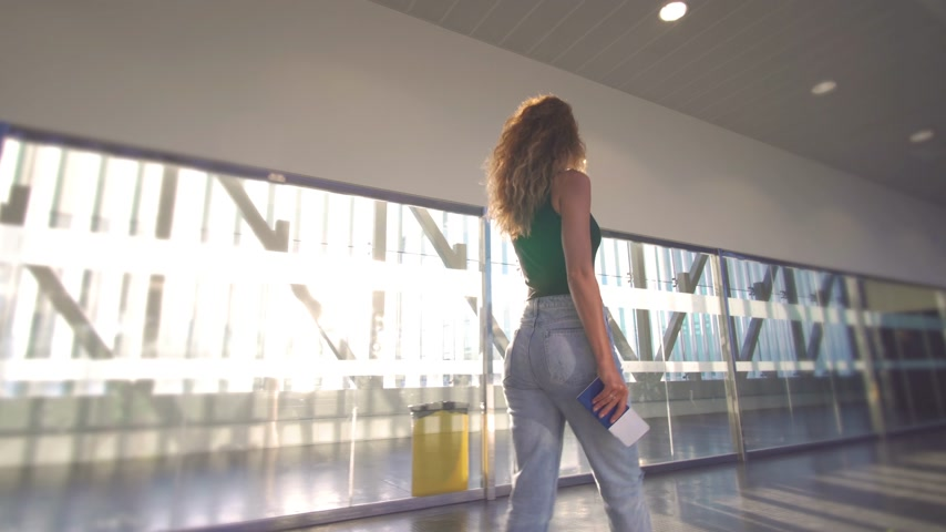 letectví : Girl standing at the window in airport before boarding the plane.