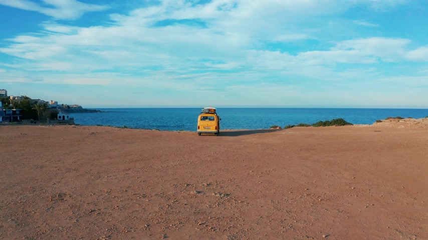 California, United States, JULY 20TH, 2019: Aerial view. Yellow VW bus van on a parking lot on a rock near the sea.