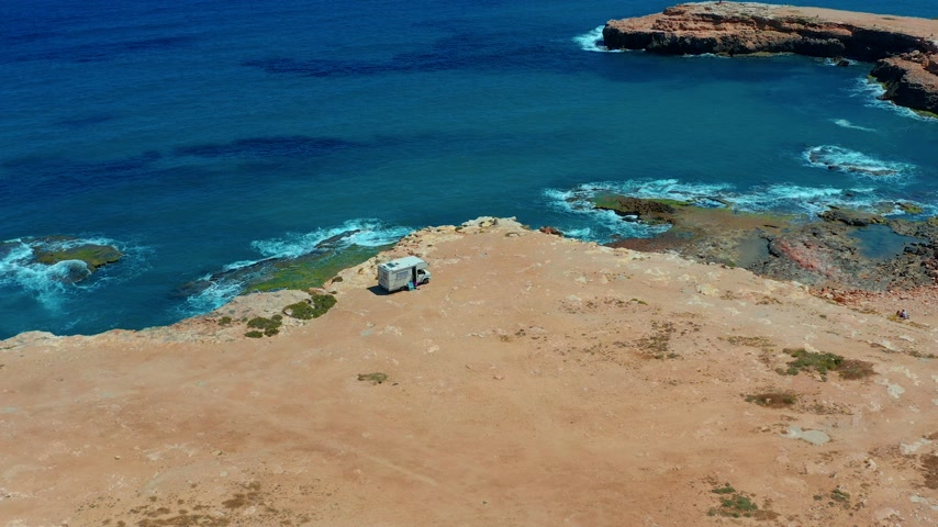 caravan : Aerial view. Camper van on a parking lot on a rock near the sea. RV park. Stock Footage