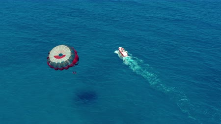 padák : Aerial view. People flying on a colorful parachute towed by a motor boat. Parasailing in blue sky. Dostupné videozáznamy