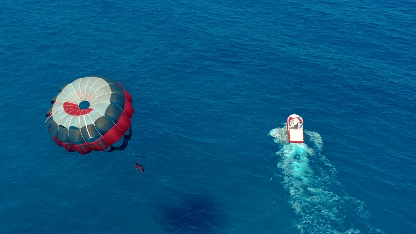 parachuting : Aerial view. Flying with Parachute Behind a Boat. Extreme Water Sport in the Sea. Parasailing. Stock Footage