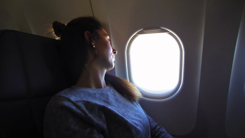 assentos : Girl at porthole in the plane. Young woman seating on passenger seat and looking out window on airplane. Stock Footage