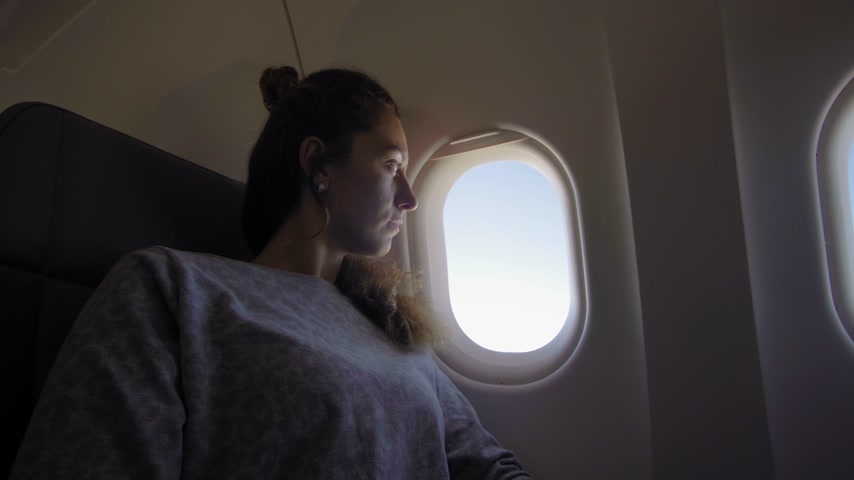 aircraft cabin : Girl at porthole in the plane. Young woman seating on passenger seat and looking out window on airplane. Stock Footage