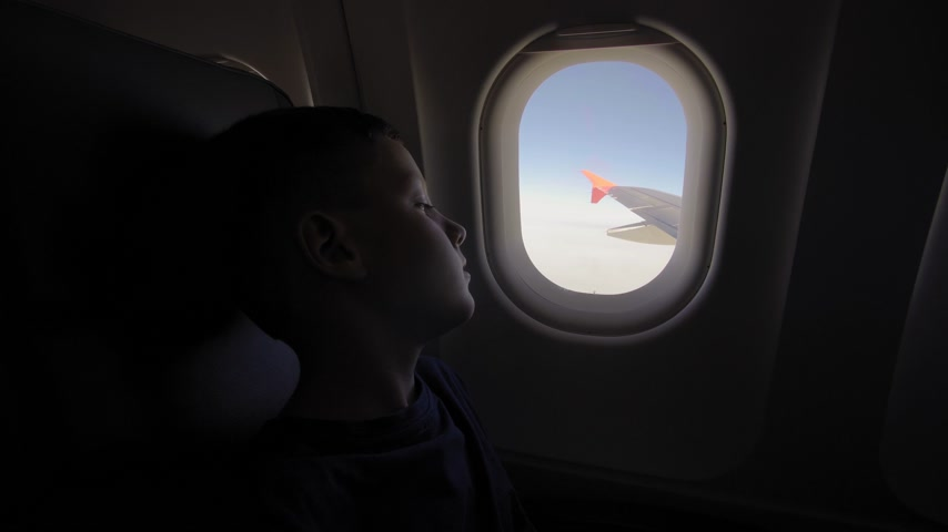 do interior : The small boy looks to the plane window to the wing plane.