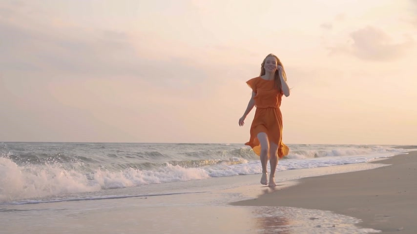 sommersprossen : The young red-haired smiling girl run in the orange dress at beach by the sea in summer.