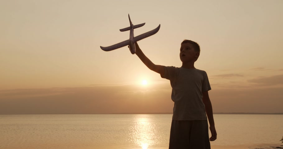 um : Happy kid playing with toy airplane against orange sun summer. Best childhood concept.