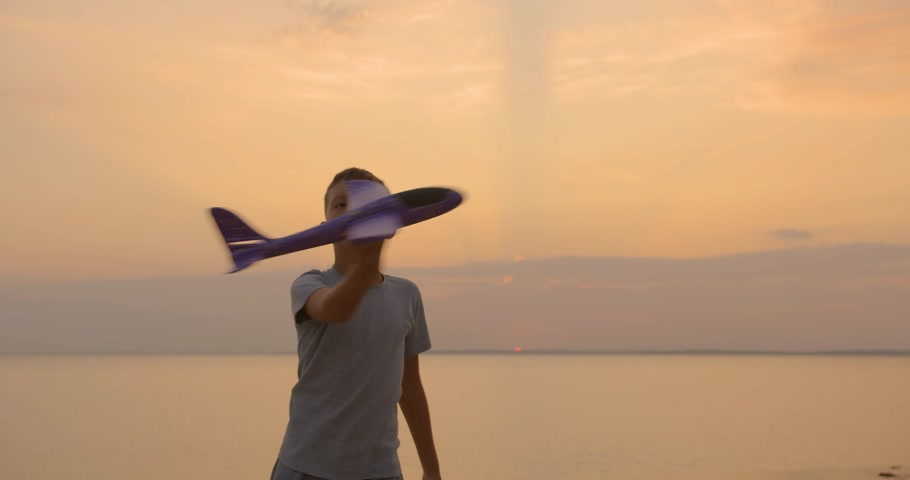 野心 : Happy kid playing with toy airplane against orange sun summer. Best childhood concept.