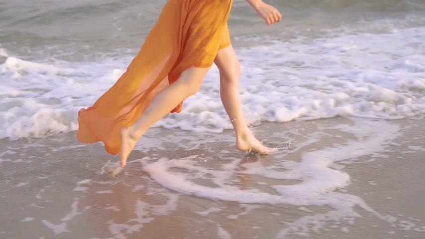 bare foot : Female bare feet and fluttering dress at sunset. Young barefoot girlrunning in long orage dress along the surf line.