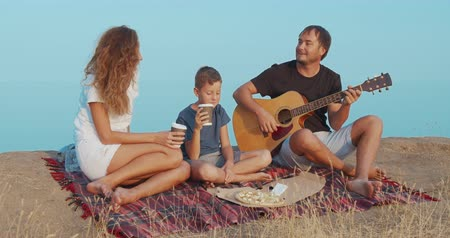 guitarrista : Family sitting by the on the beach in the evening and playing guitar.
