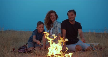 şenlik ateşi : The son and his parents roast marshmallow on sticks. Family camping on the beach in the evening. A family.