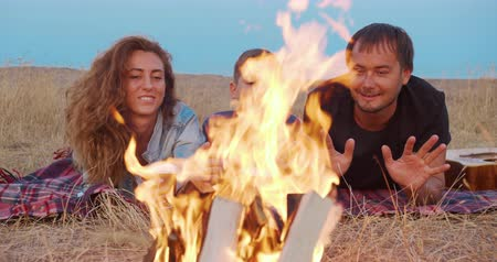 baharatlı alman sosisi : Family sitting in the evening round a bright bonfire outdoors.