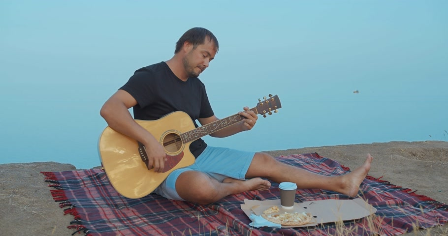 alpes : The Man playing the guitar and singing on the beach. Stock Footage