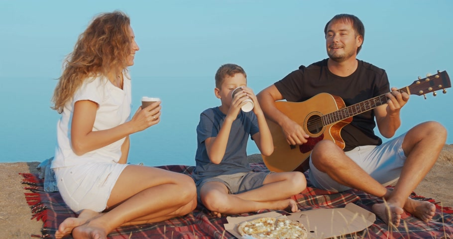 guitarrista : Family actively communicating and holding glasses with drinks while picnic on a hill.