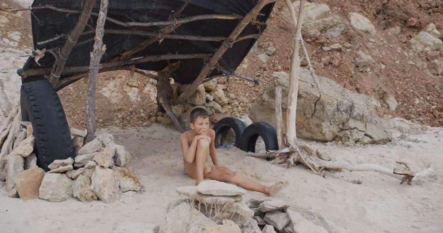 доисторический : Caveman, manly boy. Funny young primitive boy outdoors. Evolution survival concept. Calm boy outside sitting at his rocky settlement. Prehistoric tribal man.