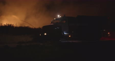 silnik : Fire truck with flashing lights on. Fire truck on background of burning grass on field during forest fire. Rescue and prevention of natural disasters. Wideo