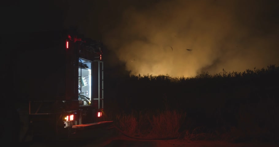 siren : Fire truck with flashing lights on. Fire truck on background of burning grass on field during forest fire. Rescue and prevention of natural disasters. Stock Footage