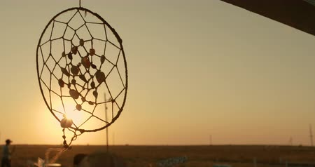 native american culture : Native American dreamcatcher hanging in breeze at sunset.