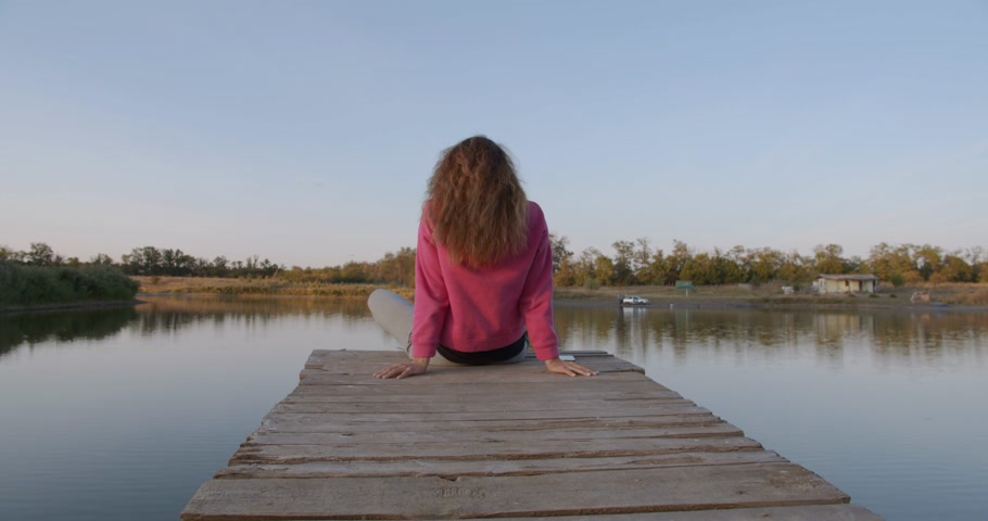 platform edge : Beautiful girl contemplates the lake sitting on the pier. Stock Footage