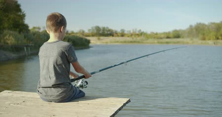 fishing pole : The boy is fishing on the old pier on the river. Stock Footage