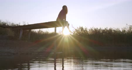 platform edge : Woman relaxes by the lake sitting on the edge of a wooden jetty , swing legs on the sunset.