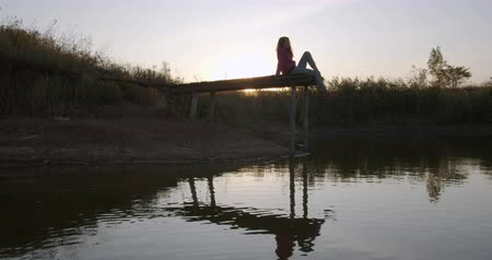 川岸 : Beautiful girl contemplates the lake sitting on the pier. 動画素材