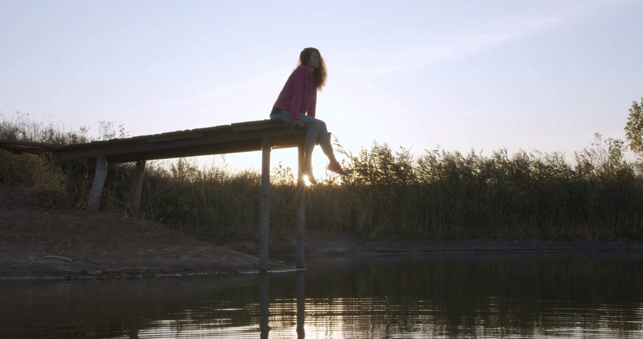 relaks : Woman relaxes by the lake sitting on the edge of a wooden jetty , swing legs on the sunset.