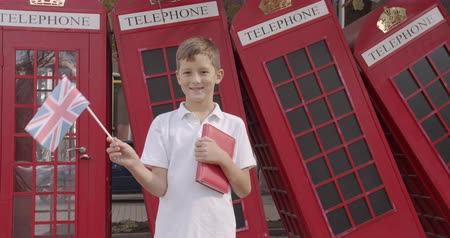 telefooncel : Slow motion portrait of cute boy waving British flag standing outdoors alone smiling looking at camera. On the background English red telephone booths. Travelling concept.