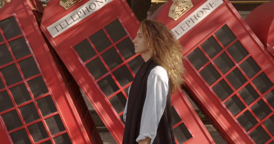 big ben : Attractive girl walking on a background of red British phones. Travel, tourist places concept.