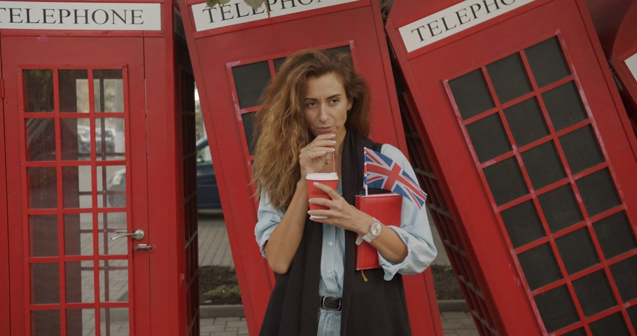 киоск : Attractive girl walking on a background of red British phones. Drinks coffee and sightseeing. Стоковые видеозаписи