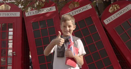 telefooncel : Slow motion portrait of cute boy standing outdoors alone smiling looking at camera. On the background English red telephone booths. Travelling concept. Stockvideo