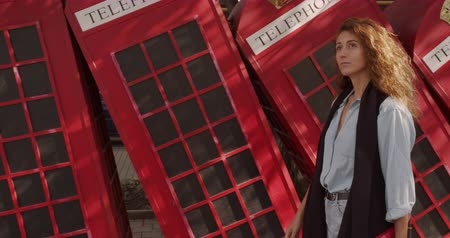 great britain : Attractive girl walking on a background of red British phones. Travel, tourist places concept.