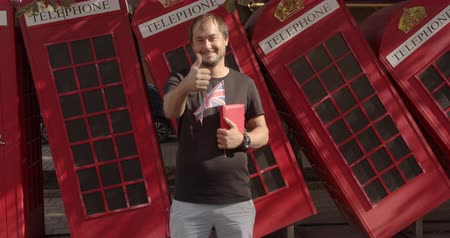 estrangeiro : Smiling man showing thumbs up, standing against British telephone, studying English. Stock Footage