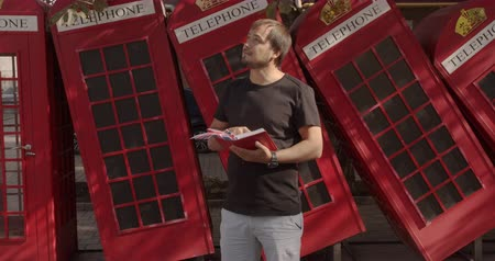 Бен : The Man on a background of red British phones. Travel, tourist places concept.