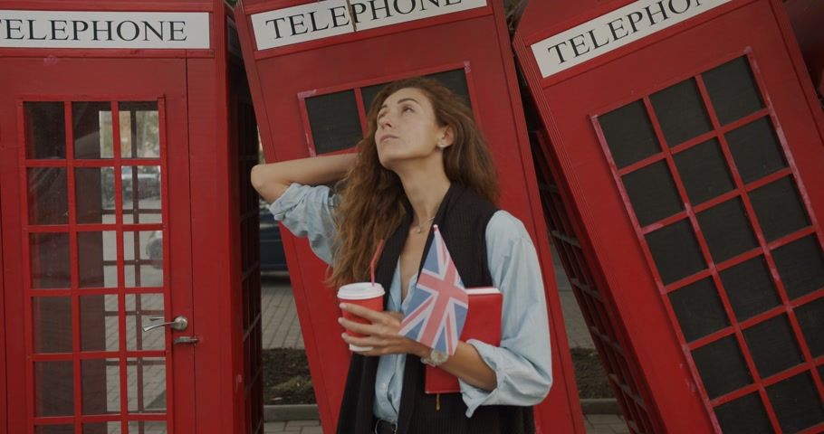 big ben : Attractive girl walking on a background of red British phones. Drinks coffee and sightseeing. Stock Footage
