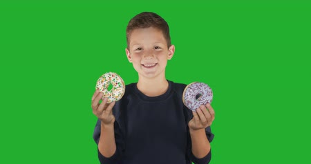 favori : Closeup. portrait of a funny guy, having fun with colorful donuts against his face. Expressions, diet concept, background color. 4k. Stok Video