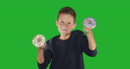 shovívavost : Closeup. portrait of a funny guy, having fun with colorful donuts against his face. Expressions, diet concept, background color. 4k. Dostupné videozáznamy