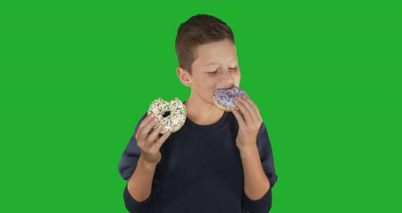favori : Closeup. Portrait of a funny guy eating colorful donuts. Expressions, diet concept, background color. 4k. Stok Video