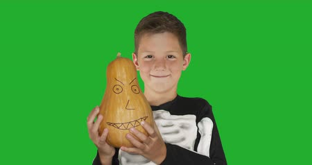 ijesztő : Little boy wearing costume with a pumkin smiling for Halloween party against chroma key green screen background.